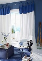 A blue and white living room with a fabric stool and a chair in a seating area in front of a balcony door with floor-length curtains