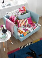 An armchair with colourful, floral-patterned cushions, a retro side table and a patterned rug in a living room