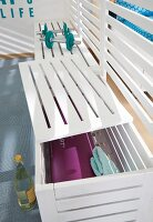 A white painted bench made from wooden slats used as a room divider and as storage for sports equipment