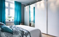 A white wardrobe with wide sliding elements and a mirrored front in a bedroom with blue curtains