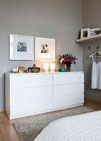Framed photos over a white chest of drawers in a bedroom with grey walls