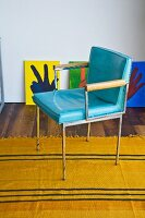 A light blue, vintage leather chair on a yellow rug
