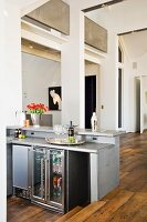 A kitchen counter with a fridge in an open-plan living room with a rustic parquet floor
