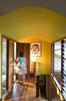 Eine Frau auf dem Flur mit Holzboden und gelben Wänden
