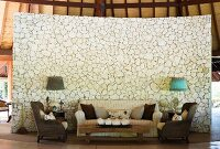 Sofa set and rustic coffee table in front of curved stylised stone partition in tropical hut