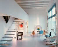 Open-plan living space with stairs and gallery and chairs in a mixture of styles