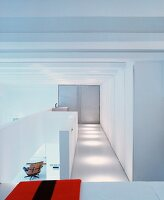 White gallery with fitted cupboards and view of armchair in living room