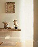 Antique Greek stone head and vessels on table with stone top