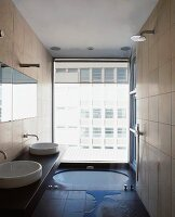 Modern bathroom with floor-level bathtub in front of floor to ceiling window