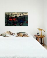 Double bed with pillows below modern artwork with ship motif