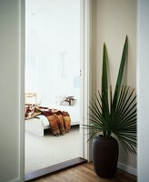Floor vase with palm leaves next to open door showing view of bed
