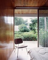 50s-style wooden chair in front of open terrace door in wood-panelled bedroom