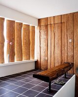 Rustic bench and vertical wooden planks on walls and in window recess