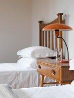 Nachttisch mit Retro Lampe zwischen Einzelbetten