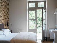 Schlafraum mit Waschbereich und offenstehender Terrassentür