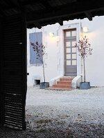Blick durch offenes Scheunentor auf Wohnhaus und Eingangstür mit Wandbeleuchtung