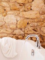 Badewanne mit einlaufendem Wasser vor Natursteinwand