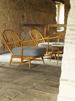 Sessel im Fiftiesstil auf altem Dielenboden im rustikalen Ambiente