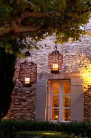 Chinese lanterns hanging from tree in front of Provençal stone house