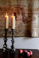 Antique candlesticks in front of tapestry