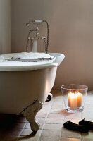 Candle lantern next to full bathtub