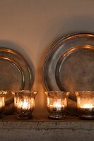 Tealight holders in front of pewter plates on mantelpiece