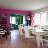 Long table and piano in dining room separated from living room by folding doors