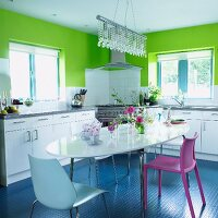 Oval dining table and various chairs in white kitchen with green wall and petrol blue rubber flooring