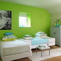 Green guest room with sofa beds and pale green cupboard