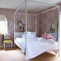 White-painted four-poster bed in bedroom with pink wallpaper