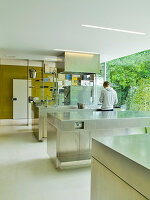 Man at free-standing kitchen counter in designer kitchen of contemporary house
