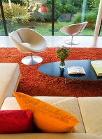 Classic coffee table and white, designer swivel chair on red, flokati-style rug in contemporary building with glass facade and view of garden