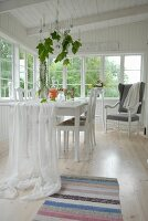 White fabric draped over dining table in loggia of white wooden house