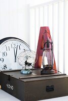 Vintage fan and oil lamp on wooden crate in front of large letter and wall clock on white surface