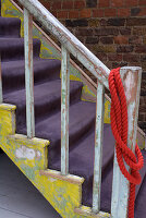 Old wooden staircase with scraped-off paint and purple velour carpet on treads