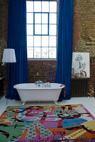 Loft bathroom with colourful rug and free-standing vintage bathtub in front of blue curtains