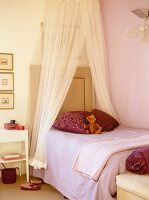 Pink girl's bedroom with canopy bed and teddy bear