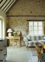 Corner of living room with rustic wooden table and sofa against stone wall