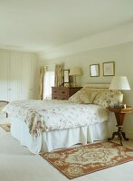 Traditional bedroom with floral throw on bed and Biedermeier-style bedside table