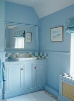 Bathroom painted light blue with fitted washstand in niche