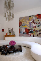 Curved, white couch in living room with varnished coffee table of gnarled, split teak; modern painting in background