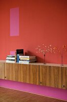 Wooden sideboard against wall in different shades of red and pink