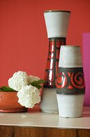 Set of 70s-style vases and white carnations in bowl against red-painted wall