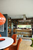 Chairs with orange upholstery in dining area in front of open-plan kitchen with island