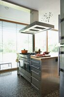 Stainless steel kitchen block with extractor hood in front of terrace windows