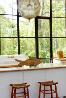 Fish-shaped, wooden ornament on modern kitchen counter and rustic barstools in front of lattice window with view of garden