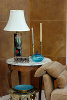 Table lamp with white lampshade and candlesticks on traditional side table in corner of room against wall clad in leather-covered panels