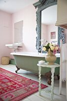Cozy bathroom in 'Shabby Style' with colorful carpet and imposing mirror above an antique bathtub