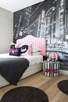 Bed with upholstered headboard against photo wallpaper mural in modern bedroom
