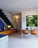 Modern, retro-style, wooden shell chairs at dining table in open-plan interior with staircase